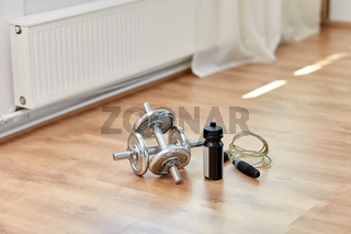 dumbbells, skipping rope and bottle on floor