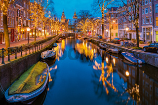 Amsterdam Netherlands canals with christmas lights during December, canal historical centre of Amsterdam at night