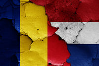 flags of Romania and Netherlands painted on cracked wall