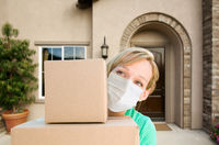 Female Holding Delivery or Moving Boxes At Front Door of House Wearing Medical Face Mask