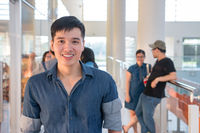 Portrait of young and handsome student smiling with friends in campus. Casual outfit of asian male in school.