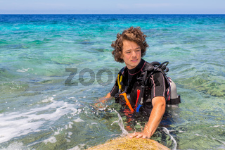 Young caucasian diver standing in blue sea