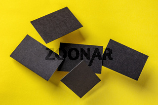 Thick black business cards levitate on a yellow paper background, a mockup