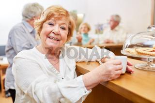 Fröhliche Seniorin beim Espresso trinken im Seniorencafe im Altenheim