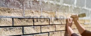 Wall cladding. Decorative bricks with rocky relief surface. Wide-angle background with copy space