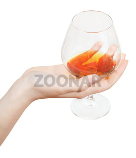 hand holds glass with brandy isolated