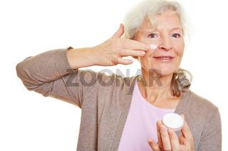 Seniorin cremt ihr Gesicht ein