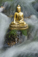 buddha sculpture is sitting in water cascade