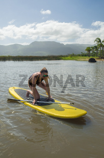 Young woman practicing Stand Up Paddle on lake, yellow board, paddling. Paddleboarding.