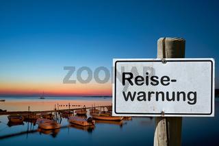 Schild mit der Aufschrift Reisewarnung in einem Urlaubszentrum