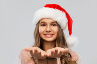 happy teenage girl in santa hat holding something