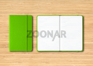 Green closed and open lined notebooks on wooden background