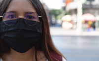 Diverse Asian girl wearing protective face mask to protect city pollution and viral respiratory Diseases - Young millennial woman using disposable surgical protection during global virus pandemic