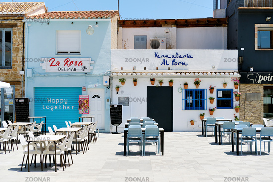 Sidewalk cafe empty tables and chairs on charming street Denia square. Spain