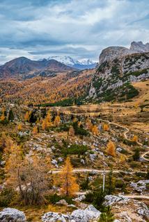 Overcast morning autumn alpine Dolomites mountain scene. Peaceful Valparola Path view, Belluno, Italy. Snowy Marmolada massif and Glacier in far.