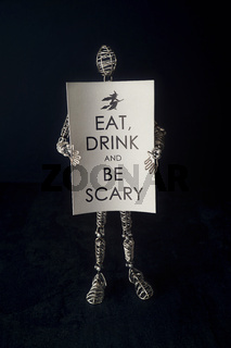 Wire mannequin holding festive halloween card