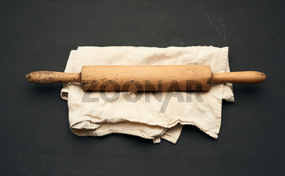 wooden rolling pin lie on a gray linen napkin, black table