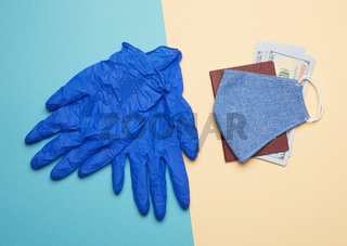 blue latex gloves and blue reusable textile mask on a beige background