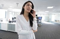 Businesswoman talking on smartphone at modern office