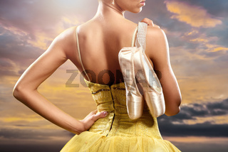 Ballerina with pointe shoes against sky background