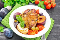 Chicken with fruits and tomatoes in plate on dark board