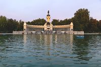 Lake at the park of Buen Retiro with monument of Alfonso XII King of Spain at sunset, Madrid, Spain