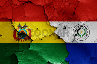 flags of Bolivia and Paraguay painted on cracked wall