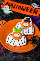 A couple (girl and boy)of funny, amusing  spiders painted on honey gingerbread. Halloween food.