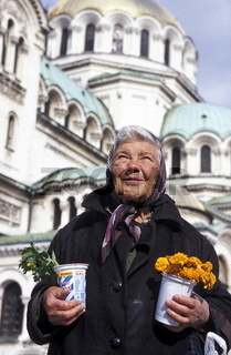 Ein alte Blumenverkaeuferin vor Kathedrale Aleksander Nevski  in der Hauptstadt Sofia an der Schwarzmeerkueste von Bulgarien.