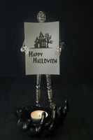 Wire mannequin holding  halloween card with candle