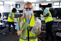 Portrait of woman wearing hi vis vest and face mask holding cleaning cloth and disinfectant