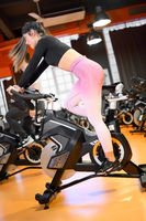 Beautiful woman cycling on a modern fitness bicycle during group spinning class at the gym