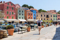 Rear view of beautiful blonde young female traveler wearing straw sun hat sightseeing and enjoying summer vacation in an old traditional costal town of Veli Losinj, Adriatic cost, Croatia