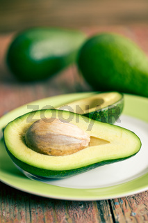 halved avocados on old wooden table