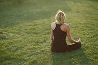Young woman doing yoga in meditation posture on a mat in the garden.