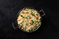 Vegetable rice, shot from the top on a black background. Basmati with broccoli, carrots and green peas