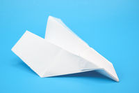 White paper plane on blue background.