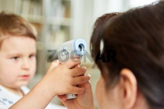 Kind und Kinderärztin üben Fieber messen