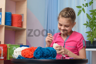 Girl knits a soft toy sitting at a table in the interior of a children's room