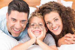 Cute young family lying on bed together smiling at camera