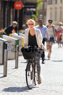 Woman riding bicycle in city center.