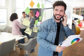 Grafikdesigner mit Smartphone im Büro