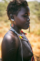 BOYA TRIBE, SOUTH SUDAN - MARCH 10, 2020: Woman in traditional colorful accessories with ritual piercing and scars looking away with sadness while standing against blurred nature in South Sudan in Africa