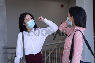Two businesswomen wearing face masks greeting each other by touching elbows at modern office
