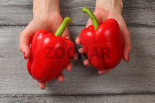 Table top view on young woman hands holding two red bell peppers above gray wood desk.