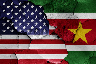 flags of USA and Suriname painted on cracked wall