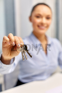 businesswoman or realtor holding keys at office