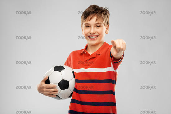 happy boy with soccer ball pointing to camera