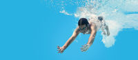Man swimming in the blue clean water. Background with copy space. Under water training and social di