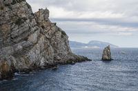 Rock with sculpture White eagle and Parus island on the background of the sea landscape and the city of Yalta. Republic Of Crimea, Russia. Cloudy day September 9, 2020